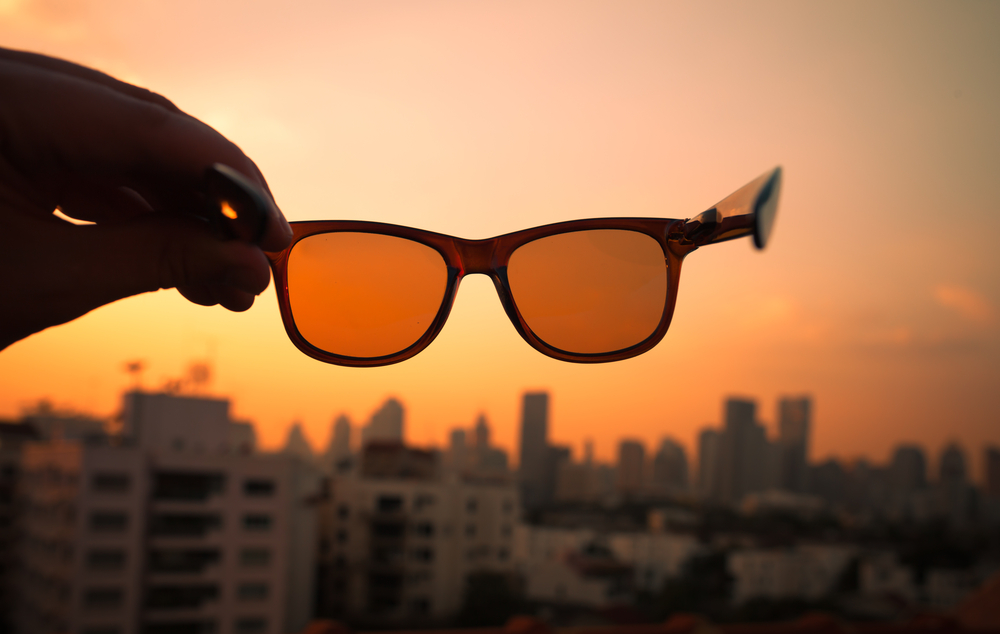 Hand Holding Sunglasses In Front Of Sunset