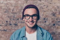 Man with glasses and knit hat in front of brick wall