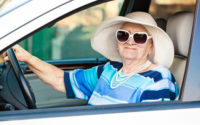 Senior woman in hat and sunglasses in car