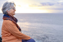 woman sitting with ocean and sunset in background