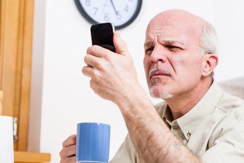 Older man struggling to read phone screen