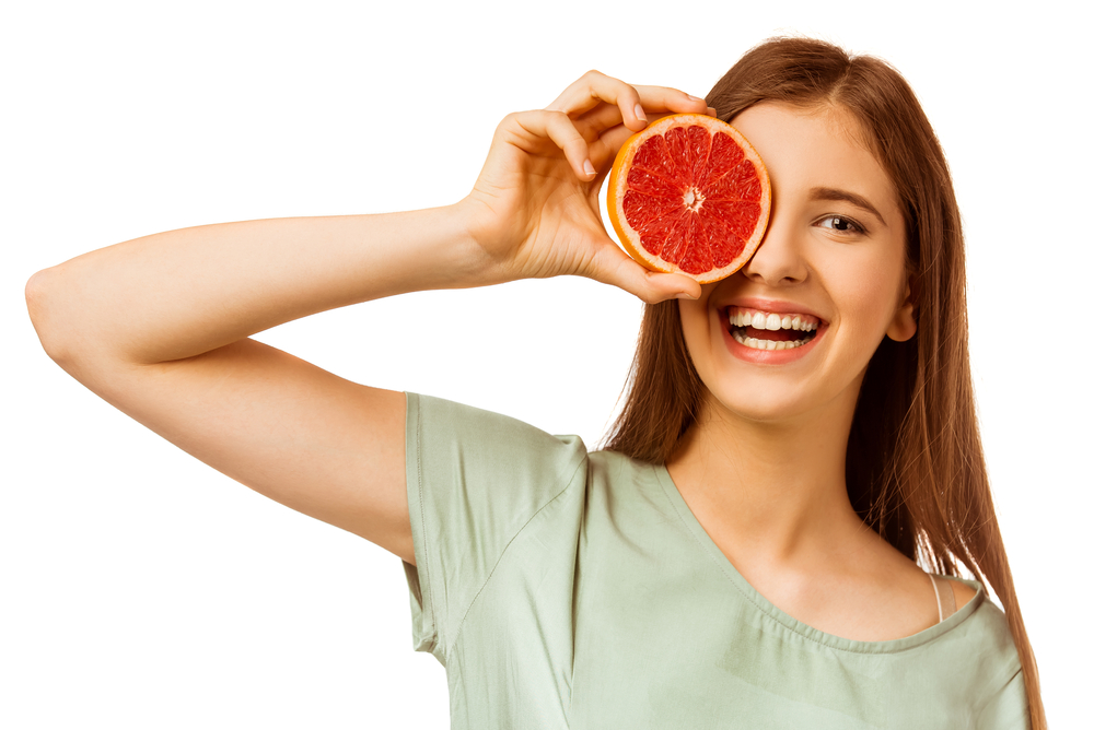 Young woman holding grapefruit in front of her eye